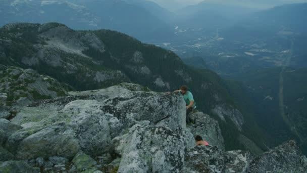 Muž horolezec dává ruku a přispívají k jeho partnerka vylézt na Mount Habrich v Kanadě Squamish údolí