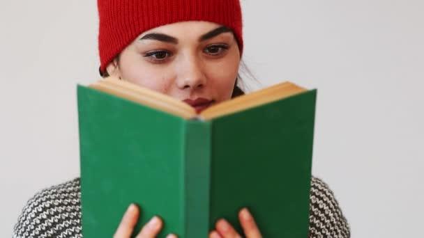 Mladá žena čte knihu na šedém pozadí