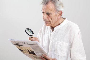 Portrait elderly man reading newspaper