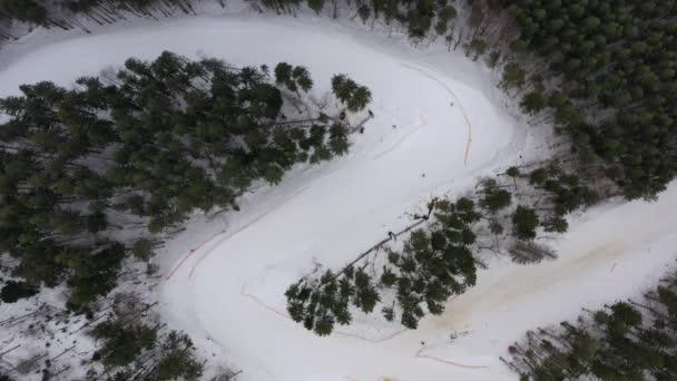 Spousta lidí sjíždí lyžování na perfektně upravených sjezdovkách v lyžařském středisku. Slunce svítí, obloha je čistá. Zpomal, 4k. Aktivní zimní rekreace a zdravý životní styl. Vrtulník, dron