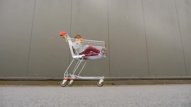 Fekete péntek háttér. Nagy értékesítési koncepció. Bevásárlási háttér. Bevásárlókocsi gyerekkel a szürke bevásárlóközpontban. Gyerekekkel vásárolok. Család bevásárlókosárral