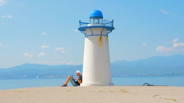 Freelancer arbeitet am Meer in der Nähe des Leuchtturms in Griechenland. leicht einen Job zu finden. Arbeitssuche in Meeresnähe. Mann sitzt mit Laptop in der Nähe des Leuchtturms am Kai. Freiberuflicher Hintergrund.
