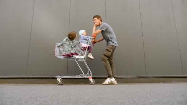 Nákupní koncept. Jedna rodičovská rodina. Otec se sourozenci jdou nakupovat, nakupovat. Šťastný táta tlačí nákupní vozík s veselými dětmi. Spotřebitelé moderního života. Pozadí brexitu