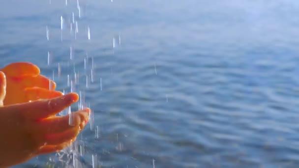 Kinderhände strecken die Wassertropfen aus. Wasser ergießt sich von oben auf kleine Kinderhände auf Meereslandschaft Hintergrund. Kleine Kinderhände reichen den Wassertropfen die Hand. Körperteil