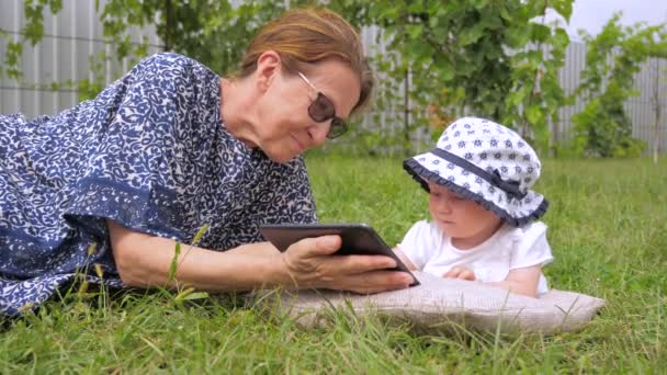 Gadgets and children. Summertime spending outdoor. Family holiday. Childhood, babyhood concept. Toddler with nanny outdoor. Grandmother with grandchild lying on green grass.