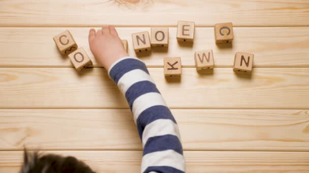 Coronavirus COVID-19 word made from wooden cubes. SARS-COV-2, Pandemic, epidemic background. Children and epidemic. Child stays at home due to COVID-19 impact. nCov-2, kids hands laying out word