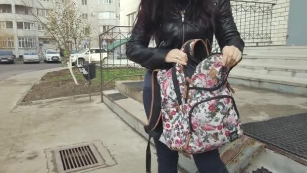 Mladá žena drží batoh a snaží se v něm něco najít na nádvoří města..