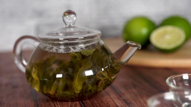 Čajové lístky se vaří ve vroucí vodě a připravují se v malé konvici. Koncept čajového dýchánku. Zelený čaj v konvici