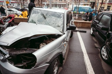 The car after the accident. Broken car on the road. The body of the car is damaged as a result of an accident. High speed head on a car traffic accident. Dents on the car body after a collision on the