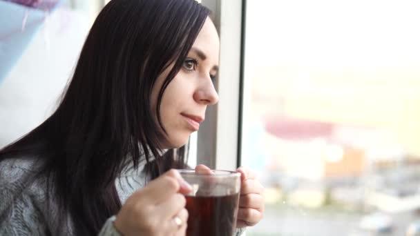 Mladá krásná žena v šedém svetru pije čaj a dívá se z okna na balkón.
