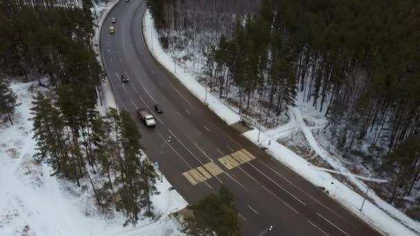 Auta na silnici v zimě se zasněženými stromy letecký pohled.