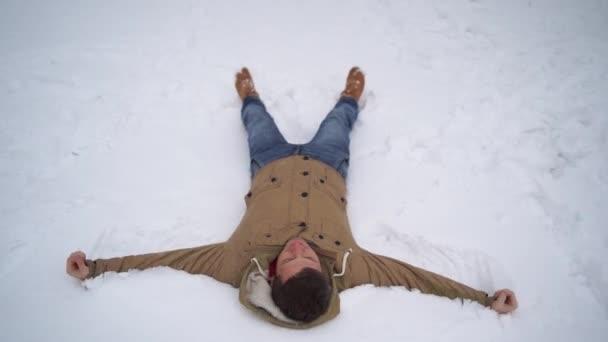 Portrét mladého muže v bundě a džínách, ležícího ve sněhu. Pohledný muž lže, rozpřahuje ruce a zavírá oči před rozkoší v zimním parku. Chlupatý sníh obklopuje všechno kolem.