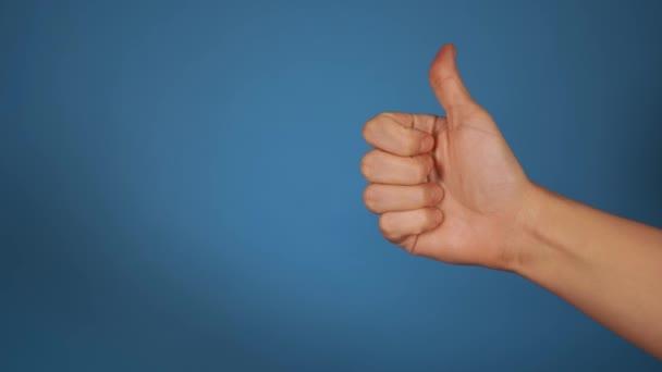 Nők kéz mutatja hüvelykujj fel a kék háttér. Egy kézifegyver, ami a jóváhagyás gesztusát mutatja. A hasonló fogalmak.