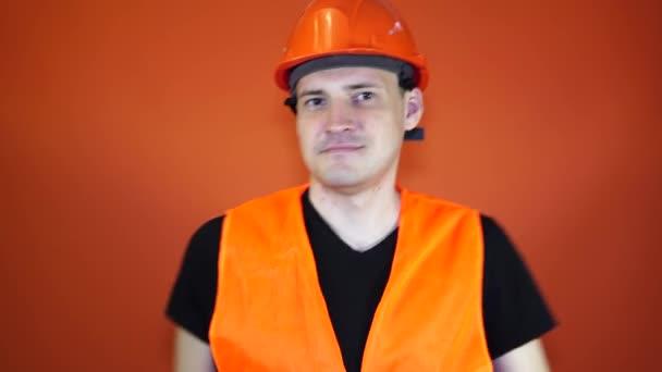 Mann in Arbeitsuniform und orangefarbenem Schutzhelm tanzt
