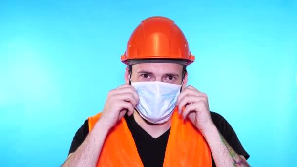 Portrét mladého muže v lékařské masce na jeho tváři na modrém pozadí. Dospělý muž zakrytý maskou, aby se chránil před nemocemi. Koncepce epidemie nebo onemocnění koronaviru.