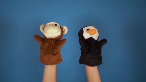 Puha babajáték kék háttérrel. A bábjáték koncepciója. Közelkép a kezét báb majom és pingvin.
