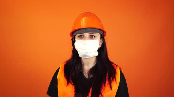 Porträt einer jungen Frau mit medizinischer Maske auf orangefarbenem Hintergrund. Erwachsene Frauen bedecken ihr Gesicht mit einer Maske, um sich vor Krankheiten zu schützen. Konzept der Coronavirus-Epidemie oder Krankheiten.