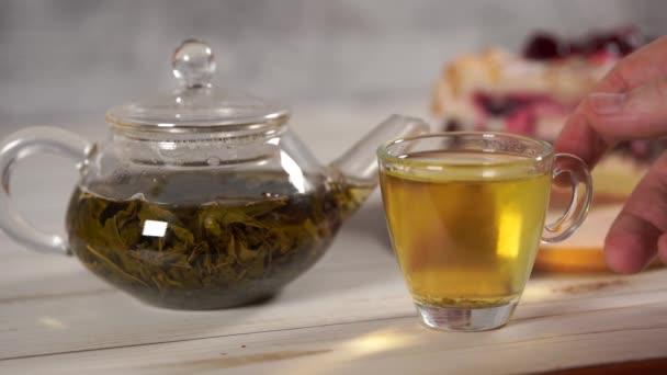 Zblízka zelený čaj v konvice a šálek na bílém dřevěném stole.