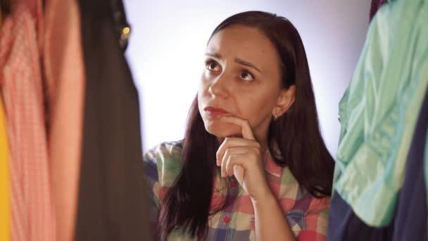 Detailní záběr mladé ženy stojící mezi oblečením a výběrem věcí v šatníku. Dospělá žena přemýšlí a hledá, co si vybrat oblečení v obchodě.