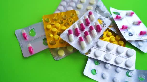 Uzavřete blistry s různými tabletami na zeleném pozadí. Mans hand selecting appropriate package of tablets. Koncepce prevence různých nemocí.