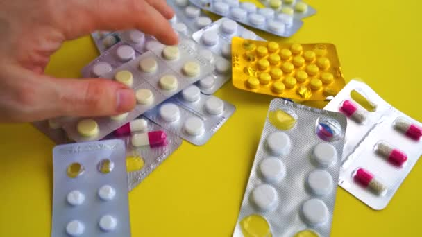 Uzavřete blistry s různými tabletami na žlutém pozadí. Mans hand selecting appropriate package of tablets. Koncepce prevence různých nemocí.