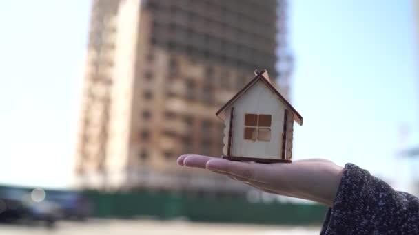 Zblízka malý dřevěný dům v ženách ruku na pozadí domu ve výstavbě. Koncept nákupu nového bytu.