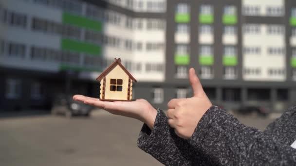 Közelkép nő kezében kis faház a kezében, és a másik kezét mutatja hüvelykujját fel a háttérben az épített ház. Új lakás vásárlásának koncepciója.