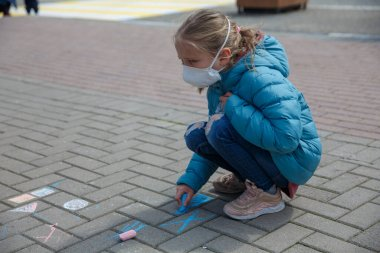 A little girl drawing with crayons wearing a medical mask, empty town on the background. A child in a protective mask. Warning of the dangers and safety quarantine measures against COVID-19
