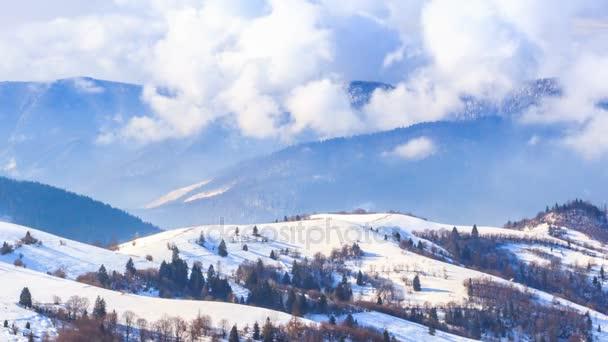 Zimní krajina. Mlha, pohybující se přes hory v zimě s modrou oblohou