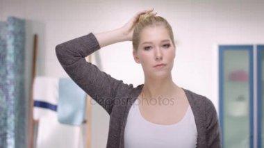 Vonzó nő megnyitja a haját egy kritikus pillantást a tükörben