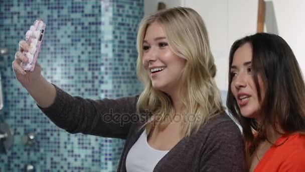 Zwei junge Frauen haben eine Menge Spaß beim Tanzen und singen in ...