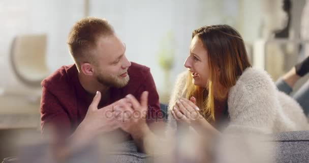 A szerelem feküdt a kanapén, és beszélgető fiatal vonzó pár