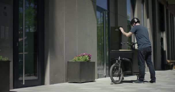 schöner Fahrradkurier entlädt sein Lastenrad