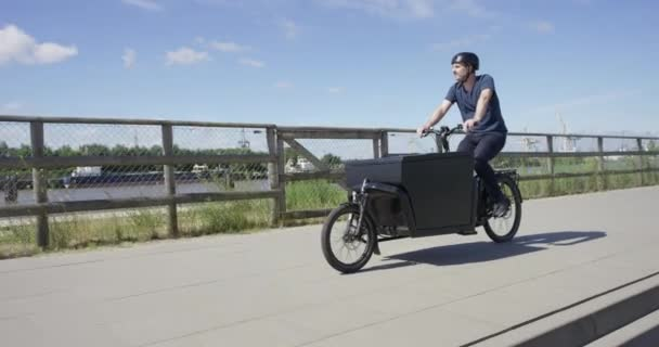 schöner Mann fährt auf schwarzem Lastenfahrrad an einem Fluss entlang