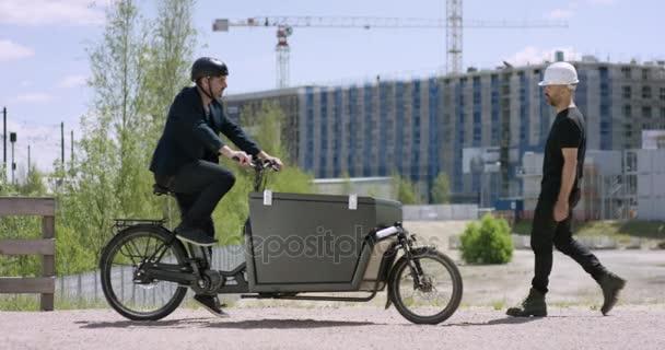 junger, gutaussehender Architekt kommt mit seinem Lastenrad auf eine Baustelle und trifft einen Bauarbeiter