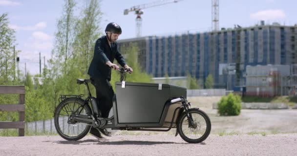 junger, gutaussehender Architekt kommt mit seinem Lastenrad auf eine Baustelle
