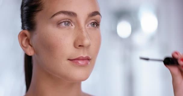 Atraktivní žena používá řasenku pro její krásné oči