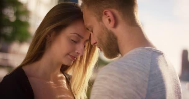 Szerelmes pár állva fejét, homlokát a naplemente előtt Hafenctiy