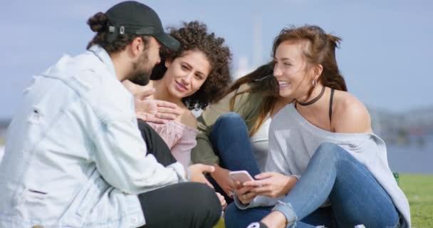 Gruppo multietnico di giovani di fuori si diverte con smartphone