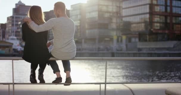 Fiatal pár csókolózás egymást a port korláton ülve