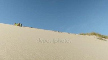Kid sliding down sand dune