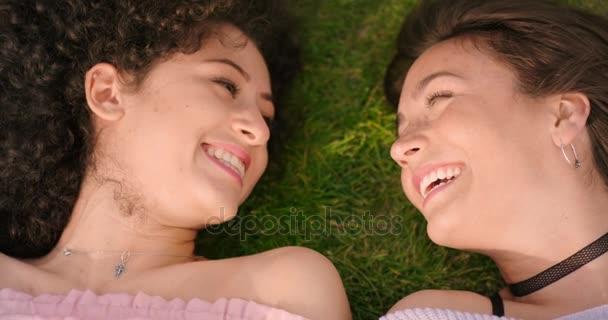 zwei junge Frauen lachend auf der Wiese liegen