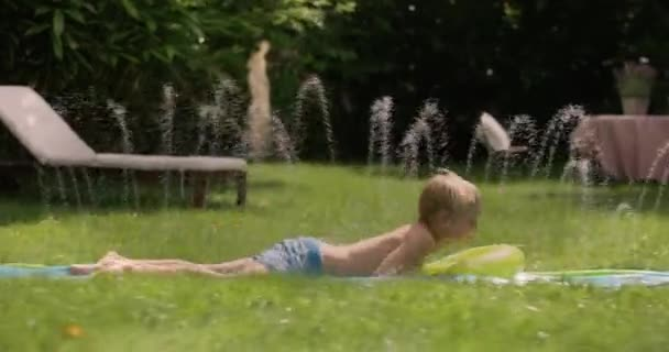 Young brothers having fun in a green garden while riding a waterslide in summer
