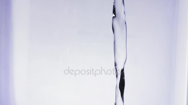 Slowmotion closeup šplouchání čerstvou vodu do sklenice