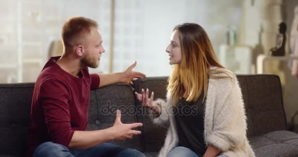 Mladý pár s drsné polemiky na gauči