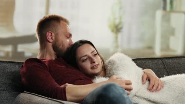 Édes a fiatal pár hozzábújva a kanapén, és beszél
