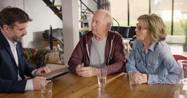 Finanzberater tippt Daten von Senioren-Paar in Tablet