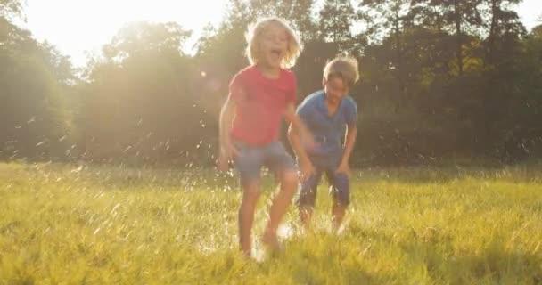 Dvě děti skákat v kaluži stříkající vodou
