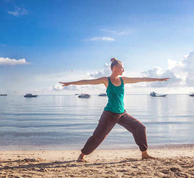beautiful young blond woman doing yoga on the shore of a tropica