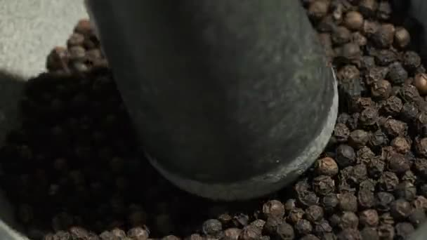 Black pepper is poured into a mortar and chopped with a pestle